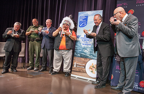Photo of representatives from Manitoba Liquor & Lotteries, the Province of Manitoba, Canada Marine Stewardship Council, Skownan First Nation, and Waterhen Lake Fisheries celebrating the announcement with taste of certified sustainable Manitoba-harvested pickerel (walleye).