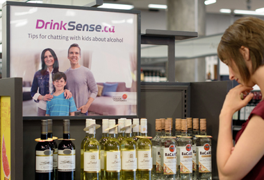 DrinkSense poster beside a woman choosing a bottle of wine.