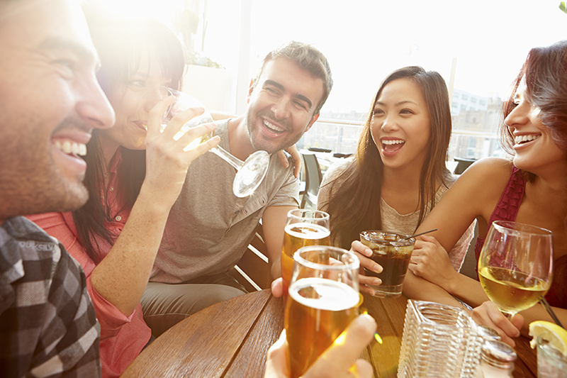 group of young people enjoying drinks outside at table