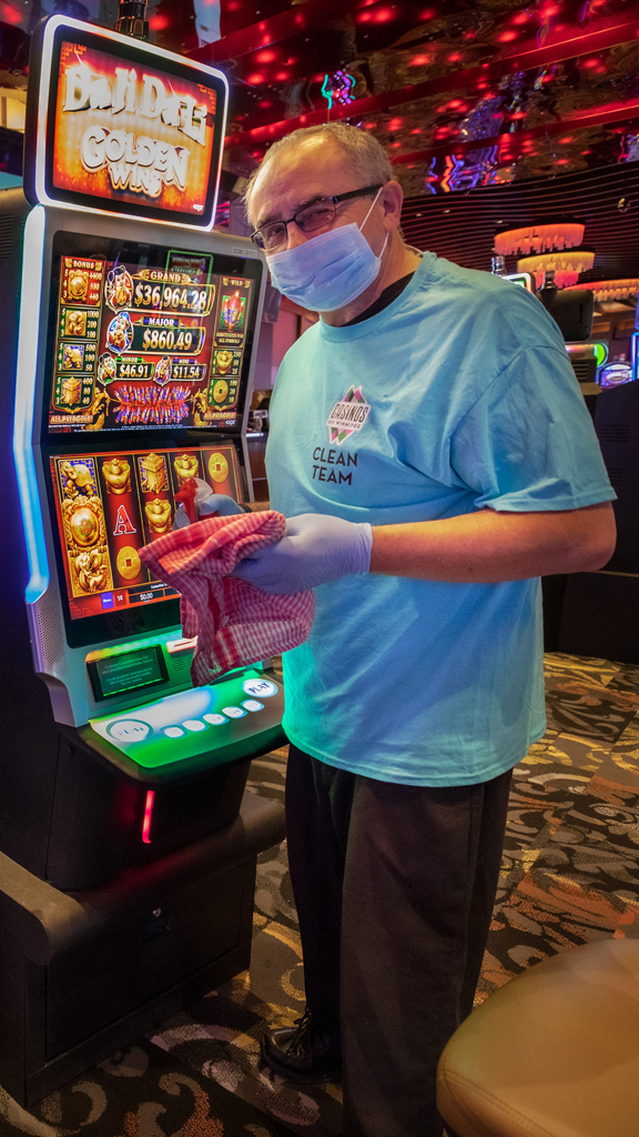 Club Regent Casino Clean Team member frequently disinfecting high-touch areas, like this gaming machine.